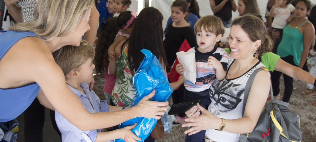Family handing another family a blue package
