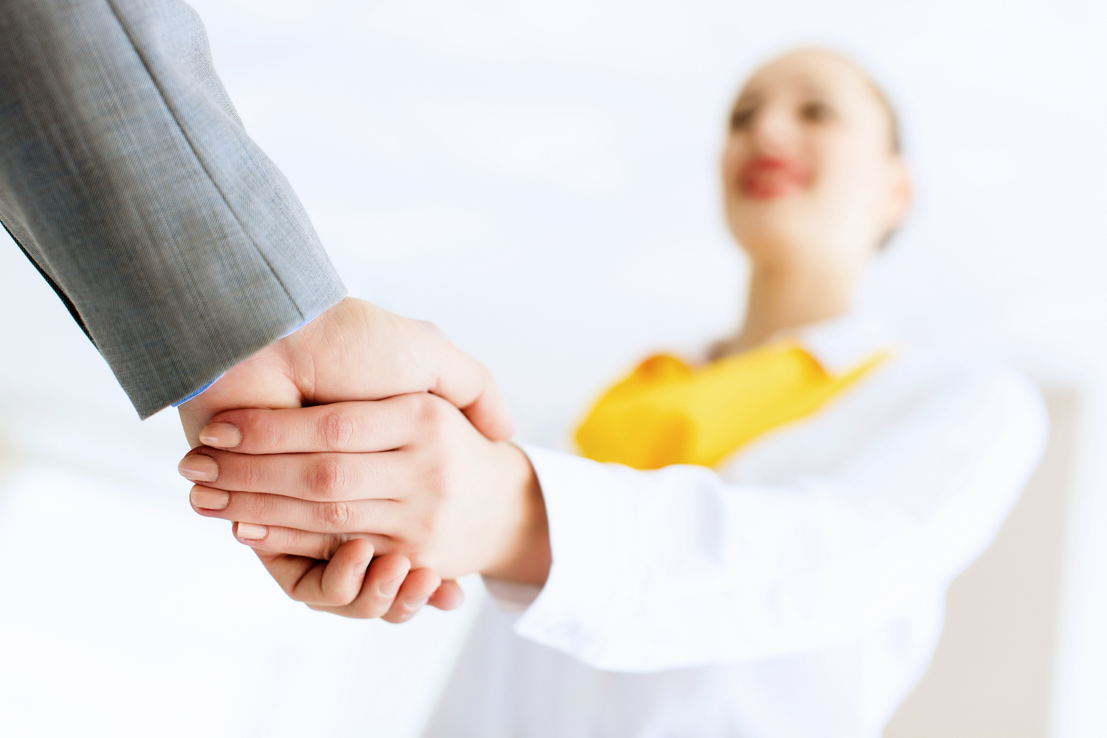 Man and woman professionals shaking hands.