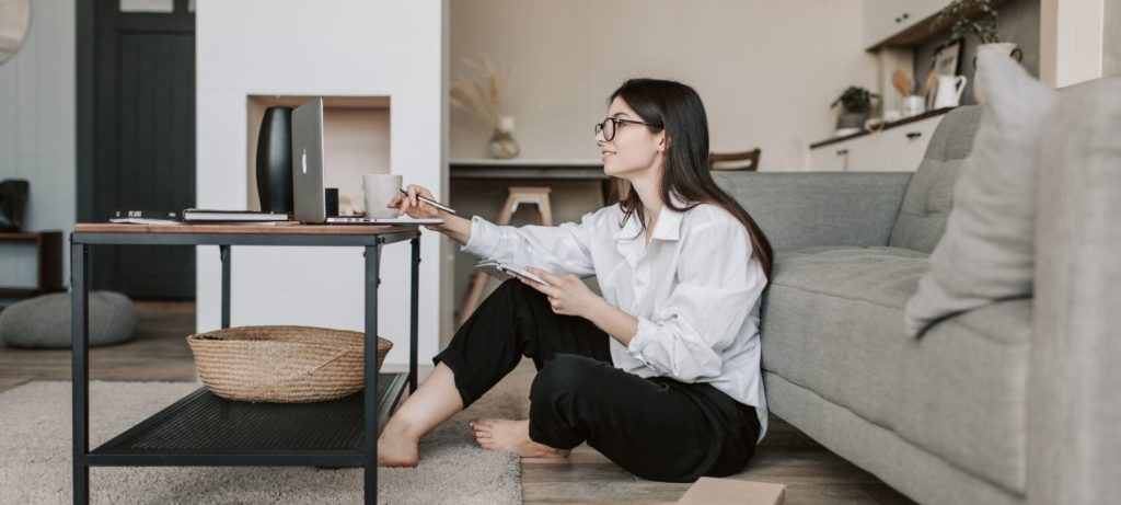 Woman sitting on floor with laptop on coffee table