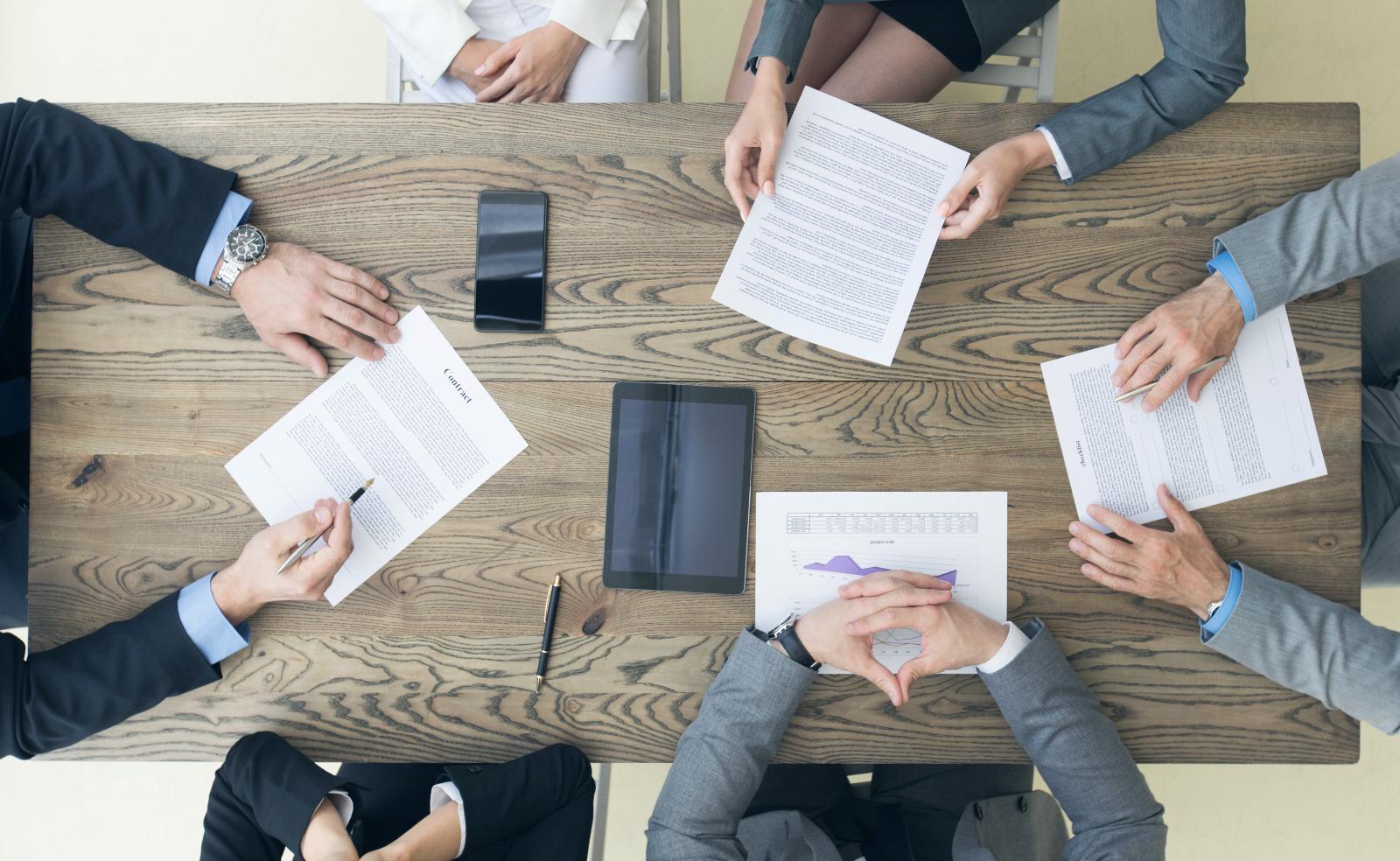 Group of people at a table reviewing a contract