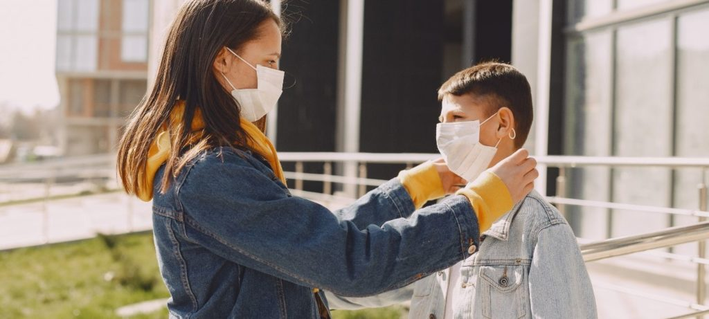 Woman helping young boy with safety mask