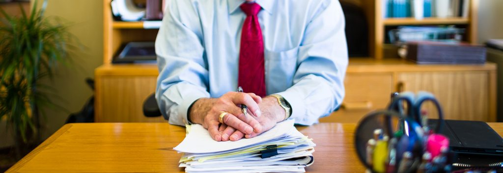A man with folded hands on a stack of papers at a desk
